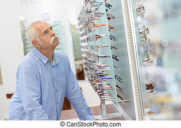 mann, kunde, wählende gläser, in, optik, kaufmannsladen