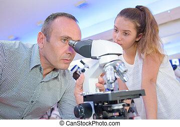 mann, mikroskop durchzusehen, junge dame, aufpassen