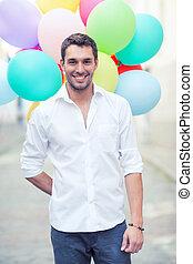 mann, mit, farbenprächtige luftballons, stadt