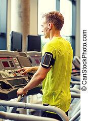 mann, mit, smartphone, trainieren, auf, tretmühle, in, turnhalle