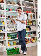 mann, prüfung, liste, auf, digital tablette, in, kaufmannsladen