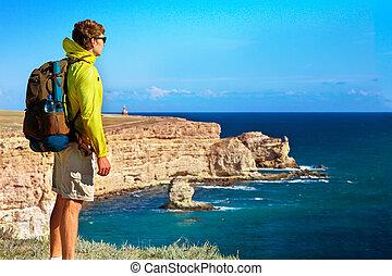 mann, reisender, mit, rucksack, entspannend, draußen, mit, meer, und, steinen, küsten, hintergrund, freiheit, und, gesunder lebensstil, begriff