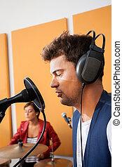 mann, singende, mit, weibliche , schlagzeugspieler, in, hintergrund