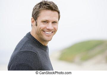 mann stehen, an, sandstrand, lächeln