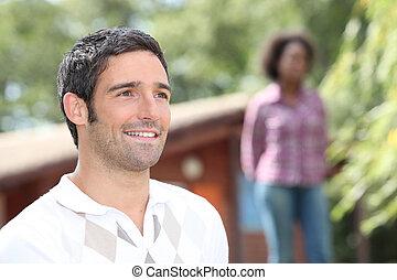 mann stehen, draußen, a, blockhaus, mit, a, frau, fokus, in, der, hintergrund