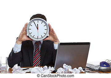 Mann under extreme time pressure holds clock in front of face