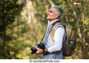 mann wandern, in, berg, mit, dslr, fotoapperat