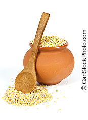 Manna croup in a clay pot with a wooden spoon on a white background