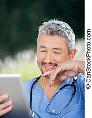 mannelijke arts, het glimlachen, terwijl, kijken naar, tablet, computer