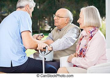 mannelijke arts, het meten van bloeddruk, van, hogere mens
