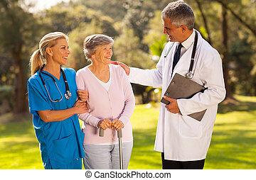 mannelijke arts, sprekend aan, het terugkrijgen, senior, patiënt