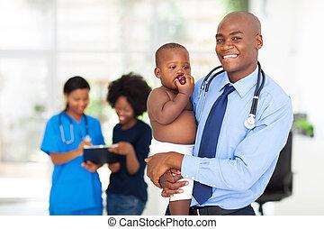 mannelijke arts, vasthoudende baby, met, moeder, en, verpleegkundige, op achtergrond