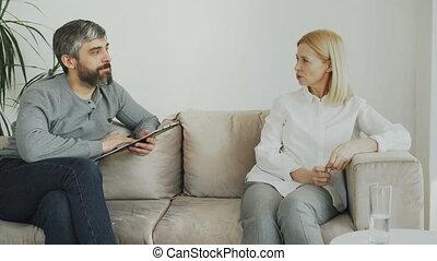 mannelijke , ervaren, psycholoog, klesten, en, het luisteren, om te, omgooien, vrouwlijk, patiënt, en, schrijfaantekeningen, op, klembord, in, zijn, kantoor