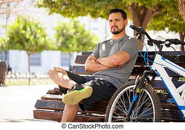 mannelijke , fietser, zittende , in, een, parkeer bank
