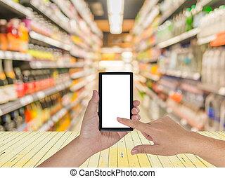 mannelijke , hand, is, vasthouden, een, moderne, aanraakscherm, telefoon, en, benevelde beeld, van, supermarkt, .