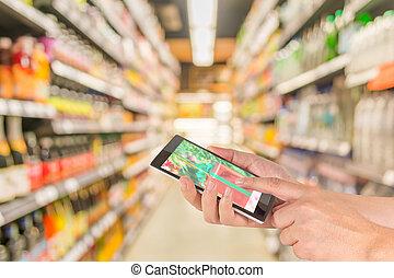 mannelijke , hand, is, vasthouden, een, moderne, aanraakscherm, telefoon, en, benevelde beeld, van, supermarket.