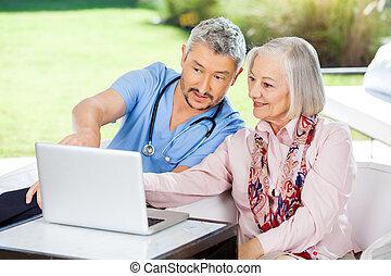 mannelijke , huisbewaarder, helpen, oude vrouw, in, gebruikende laptop