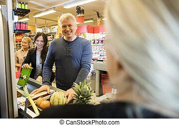 mannelijke , klant, staand, op, checkout logenstrafen, in, supermarkt