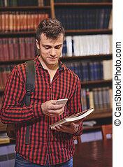 mannelijke student, gebruik, mobilephone, in, bibliotheek