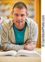 mannelijke student, met, boek, op, de, universiteit, bibliotheek, vloer