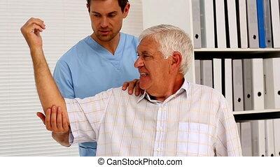 mannelijke , verpleegkundige, het tonen, bejaarden, patiënt, hoe, aan oefening