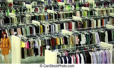 Mannequin and lot of clothes in large shop, shown in motion