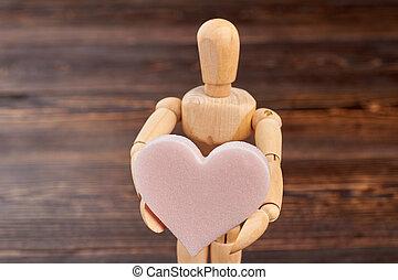 Mannequin holding heart shaped sponge.