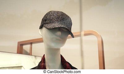 Mannequin wearing elegant grey women cap stands behind glass of large show window in contemporary fashion store closeup