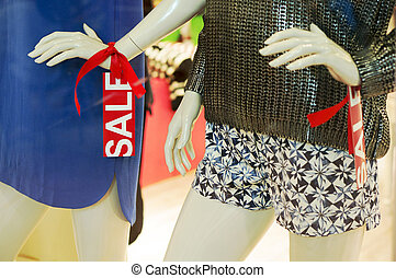 Mannequin in fashion window display with red sale tag