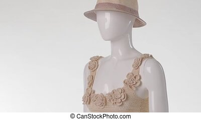 Mannequin in knitted top turning. Wicker hat and knitted...
