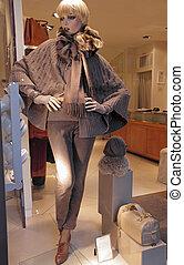 mannequin in shop window dressed in winter warm grey...