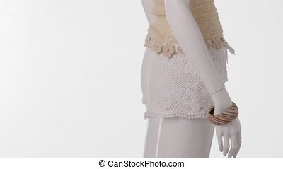 Mannequin in white shorts turning.