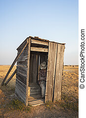 Mannequin sitting in old wooden outhouse