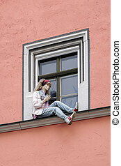 Mannequin sitting on a windowledge in Weimar