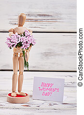 Mannequin with flowers and card. Happy women's day to you.