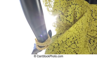 Mannequin with yellow clothes behind the glass in the...