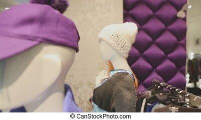 mannequins in a shop window dressed in trendy designer clothes.