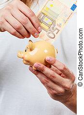 mannetje hands, met, bankbiljet, en, piggybank