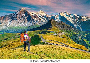 Mannlichen tourist station with backpacker hiker woman, Grindelwald, Switzerland, Europe