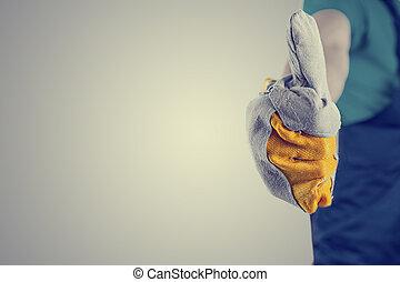 mano, en, un, guante protector, elaboración, pulgares arriba, señal