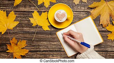 mano femenina, escritura, algo, en, cuaderno, cerca, taza, de, coffee.