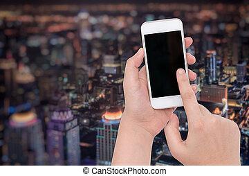mano femenina, tenencia, un, teléfono, en, borroso, noche, empresa / negocio, ciudad, plano de fondo