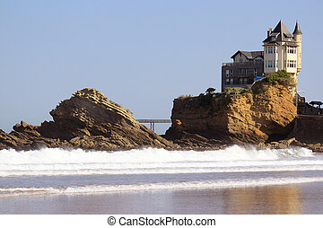 Manor - An old mansion perched on a rock in the ocean near a...