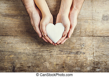 manos, de, hombre y mujer, tenencia, un, corazón, juntos.