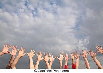 manos levantadas, en, cielo nublado, plano de fondo