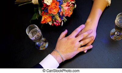 Man's and woman' hands on the table in cafe - wedding concept