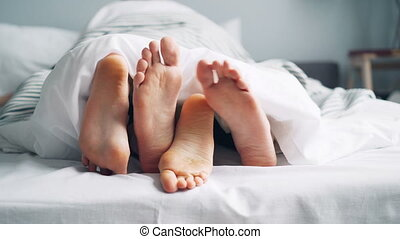 Mans and womans feet moving under blanket caressing touching...