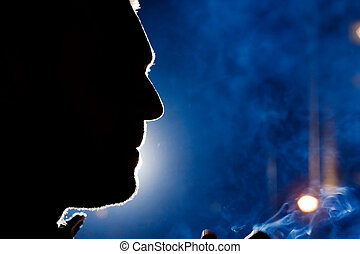 Man's face silhouette at night, dramatic light, close-up.