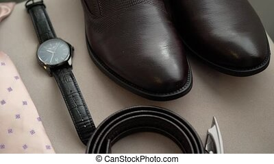 Man's fashion: brown shoes, belt, wrist watches and pink tie...