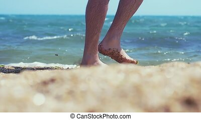 Man's feet barefoot walking along the sandy beach of the sea, slow motion. 1920x1080, hd